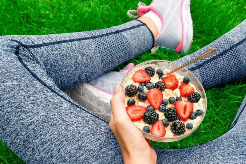 Young girl eating a oatmeal with berries after a workout . royalty free stock photo