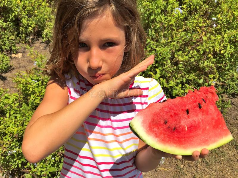 Young girl eating watermelon outdoors stock image