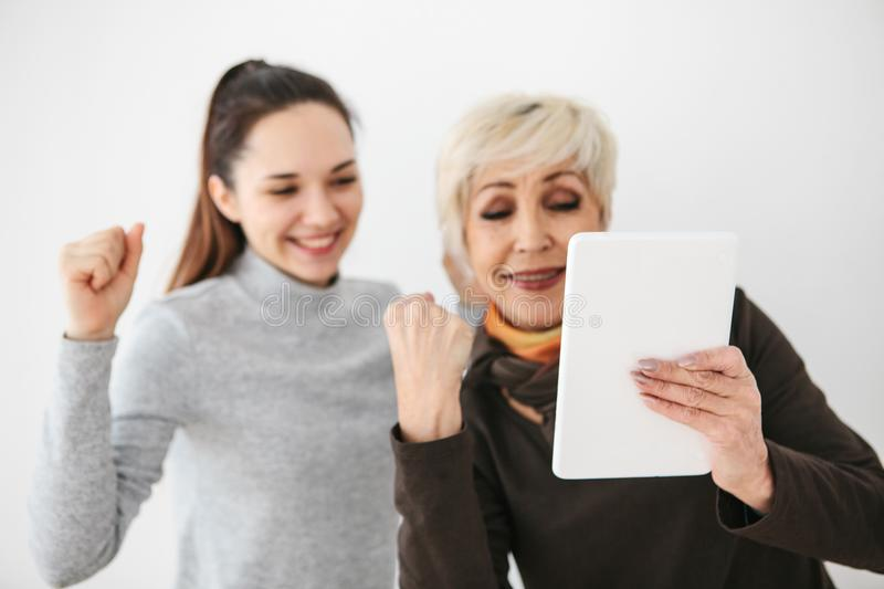 A young girl and an elderly woman look at something interesting on the tablet and are happy. Communication, joint. A young girl and an elderly women look at stock photography