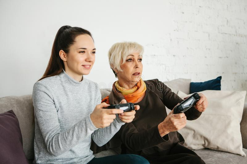 A young girl and an elderly woman play together in a video game. Joint pastime. Family life. Communication of the royalty free stock photos