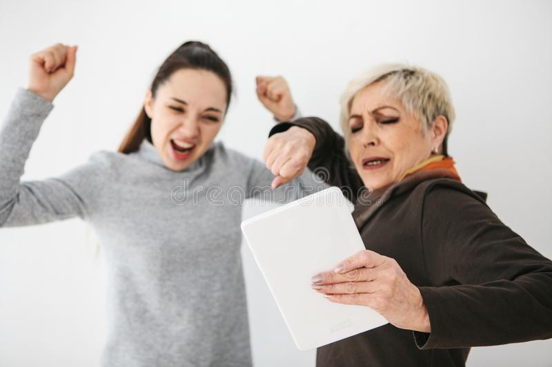 A young girl and an elderly woman look at something interesting on the tablet and show emotions. Communication, joint stock photos