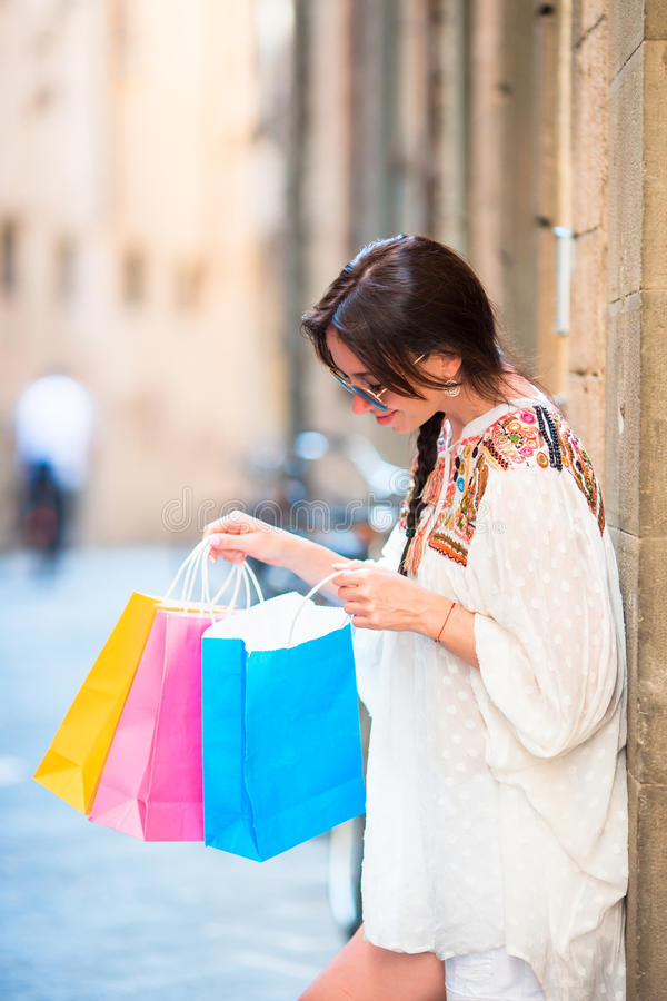 Young girl enjoy her shopping in Europe. Portrait of a beautiful happy woman holding shopping bags smiling. Young girl with shopping bags on narrow street in royalty free stock image
