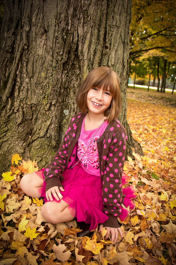 Young Girl Enjoying Autumn. Young girl sitting in the autumn leaves stock photos