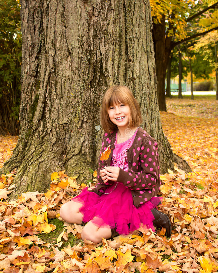 Young Girl Enjoying Autumn. Young girl sitting in the autumn leaves royalty free stock images
