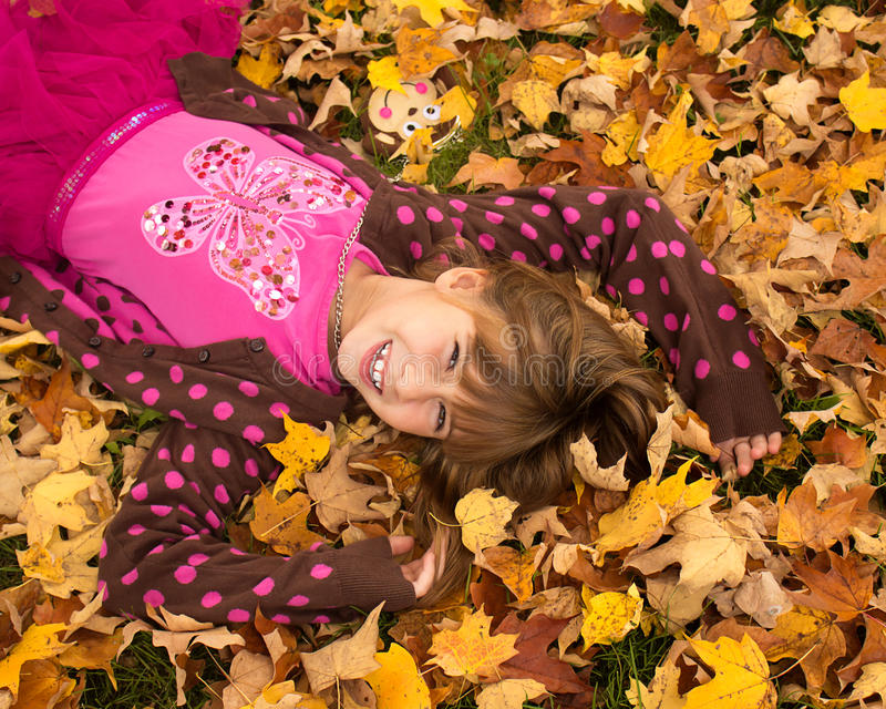 Young Girl Enjoying Autumn. Young girl laying in the autumn leaves royalty free stock photography