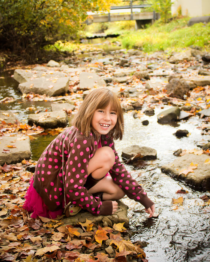 Young Girl Enjoying Autumn. Young girl playing in a stream royalty free stock photos