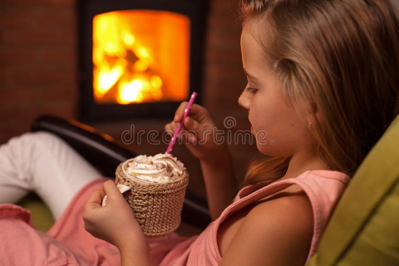 Young girl enjoying a hot chocolate in front of the fireplace stock images
