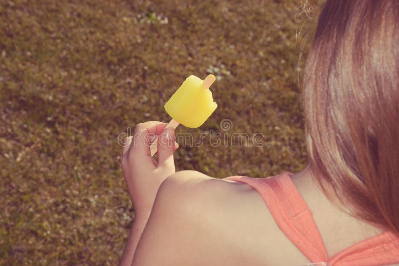 A young girl enjoys a cold yellow ice pop in hot summer on the lawn stock images