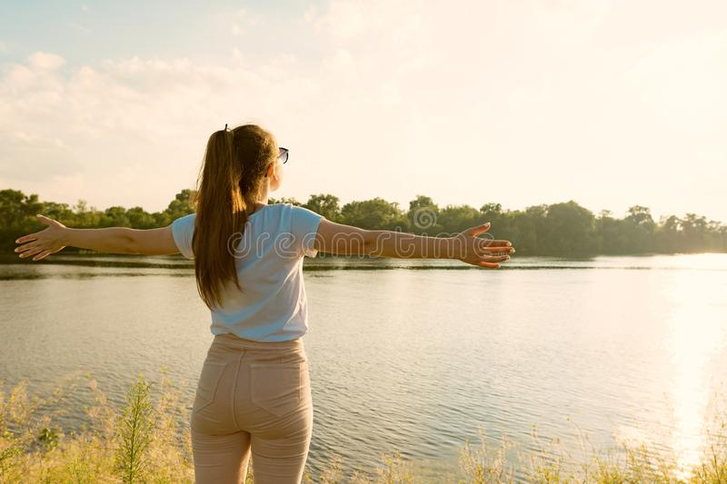 Young girl enjoys the sunset on the river beautiful landscape, the back of a girl spread her arms to the sides, golden hour.  stock photos