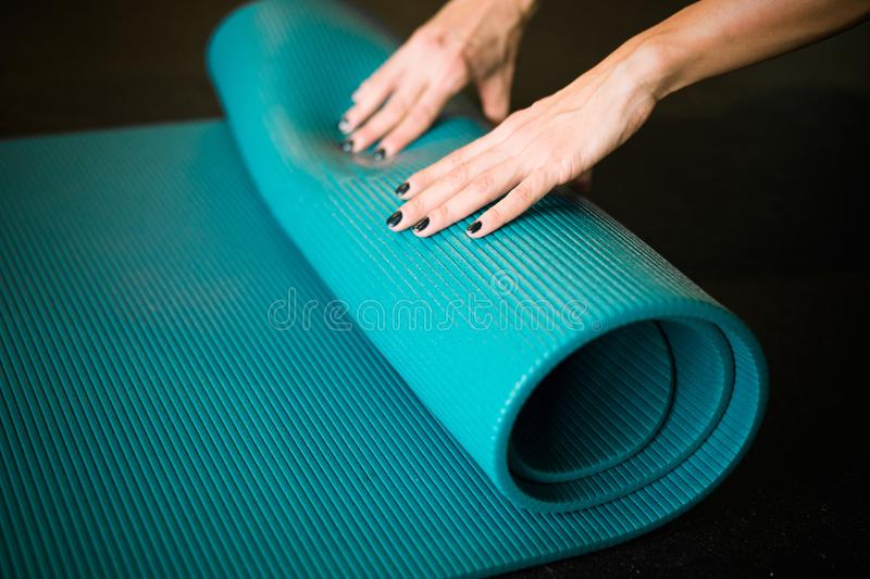 Young girl enrolling blue yoga mat after practicing workout and crossfit. Blurred background and young woman is on focus and on foreground royalty free stock image
