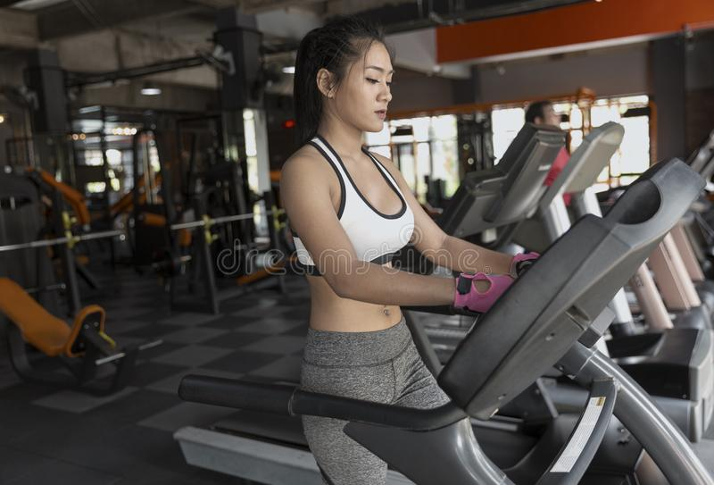 Young girl exercise bike cardio workout at fitness gym stock image