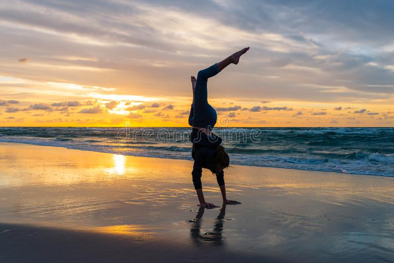 Young girl exercising on a seaside beach at sunset. Barefoot, woman, exercise, female, fitness, lifestyle, healthy, nature, ocean, sunrise, yoga, water, sky stock photography