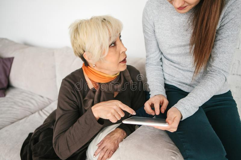A young girl explains to an elderly woman how to use a tablet or shows some application or teaches you how to use a. A young girl volunteer or granddaughter stock image