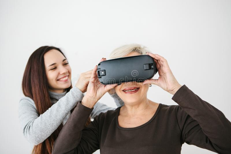 A young girl explains to an elderly woman how to use virtual reality glasses. The older generation and new technologies. A young girl explains to an elderly stock photo