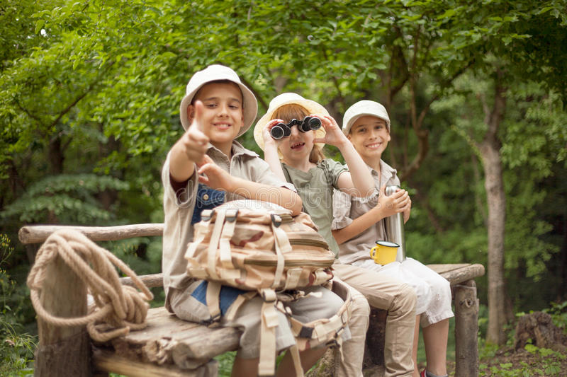 Young girl explores the nature with binoculars. Excited children on a camping trip stock image