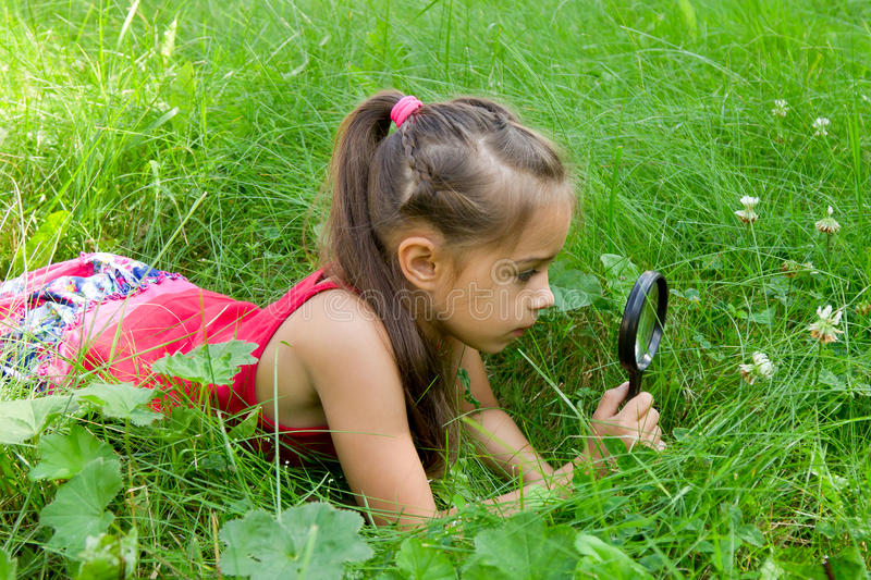 Young girl exploring nature looking at magnifying glass stock photography