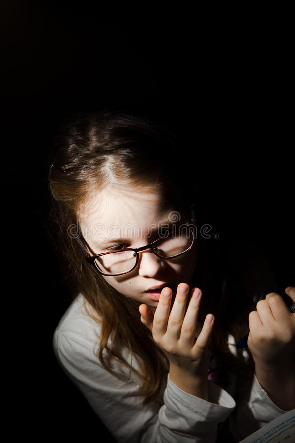 Scared young girl reading a book. Young girl feared while reading book. Black background. Fear worries and scare. Naturally processed photo stock photos