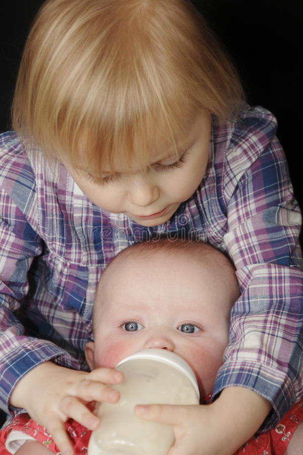 Young girl feeding baby sister. Adorable young blond girl feeding her baby sister her bottle against a black background royalty free stock image