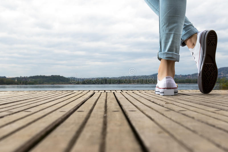 Young girl feet with shoes and blue jeans on a wooden pier royalty free stock photos