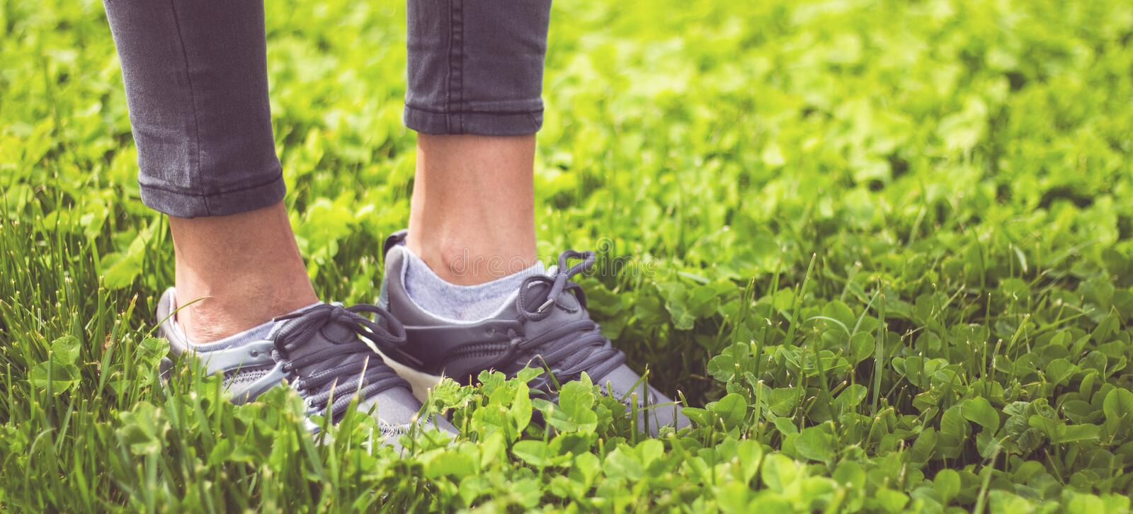 Young girl feet in sport shoes sneakers on green grass on meadow. In spring. Lifestyle and fitness stock photo