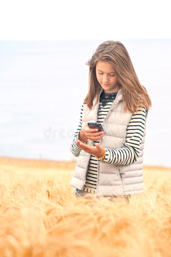 Young girl in field taking picture of wheat by smartphone stock images