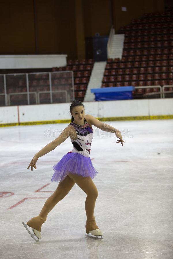 Young girl a figure skater in purple dress on an ice arena royalty free stock photos