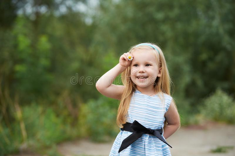 Young girl with flower. Blue dress. Smiling blond royalty free stock photos