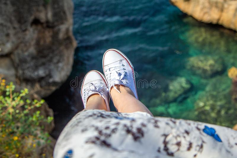 A young girl in a fluttering dress and sneakers sits on a cliff above the sea stock photo