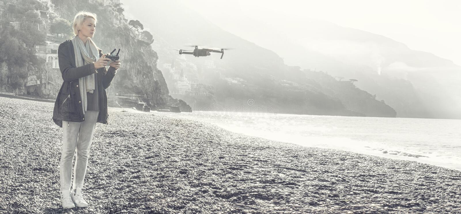 Young girl flying drone over italian coast. royalty free stock photos