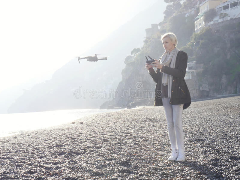 Young girl flying drone over italian coast. stock images