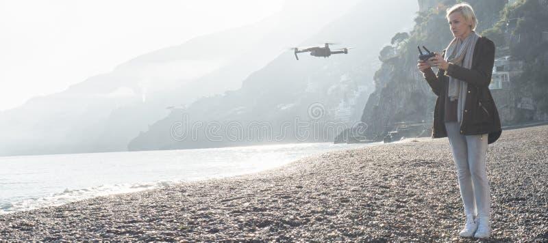 Young girl flying drone over italian coast. stock photo
