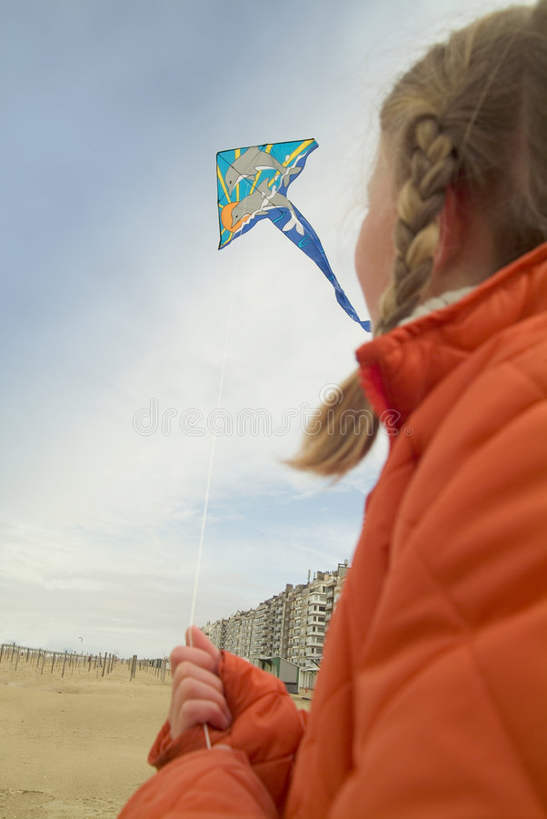 Young girl flying a kite on the beach stock images