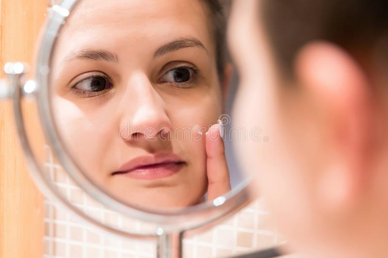 Young girl in front of a bathroom mirror putting cream on a red pimple. Beauty skincare and wellness morning concept.  royalty free stock photos