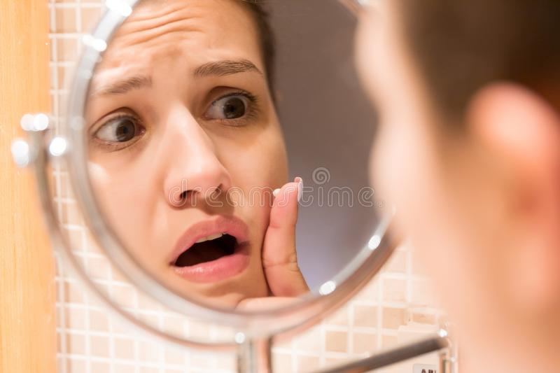 Young girl in front of a bathroom mirror putting cream on a red pimple. Beauty skincare and wellness morning concept.  royalty free stock images