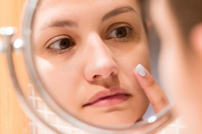 Young girl in front of a bathroom mirror putting cream on a red pimple. Beauty skincare and wellness morning concept.  stock photo