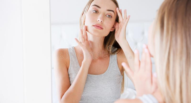Young girl front of mirror in bedroom putting cream on her face.  stock images