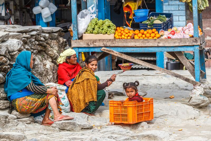 Young girl in a fruit box with family at their market stall stock photo