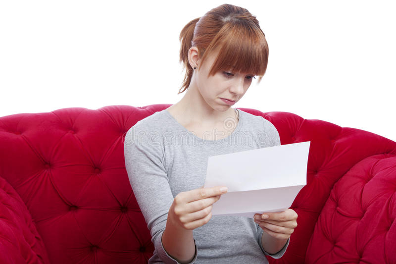 Young girl get bad news on red sofa royalty free stock photography