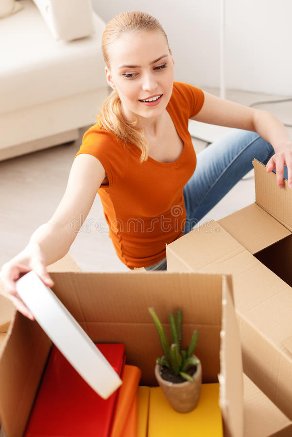 Young girl gets out wall clock of cardboard box stock photography
