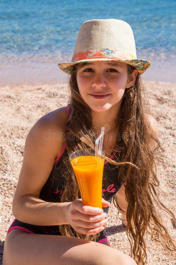 Young girl with glass of juice sitting on beach stock photography
