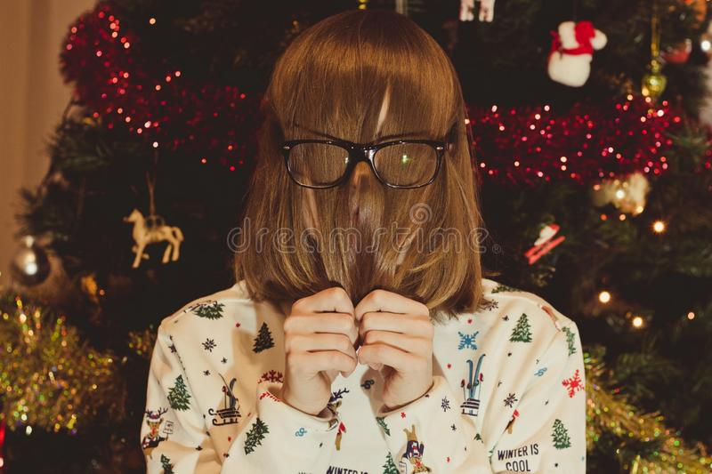 A young girl in glasses on the background of a Christmas tree dressed in a white sweater with New Year`s thematics. stock image
