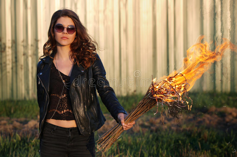 Young girl with glasses and a bully black jacket holding the torch outdoors stock photo