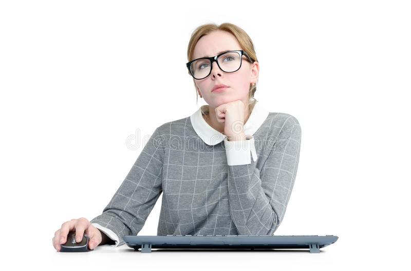 Young girl with glasses and keyboard in front of computer on white background stock images