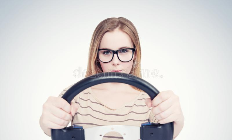 Young girl in glasses with steering wheel, auto concept.  royalty free stock images