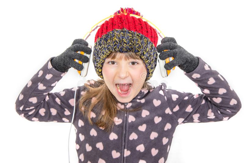 Young girl with gloves and woolen hat is listening music with headphone royalty free stock photography