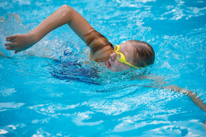 Young girl in goggles and cap swimming crawl stroke style. In the blue water pool stock photo