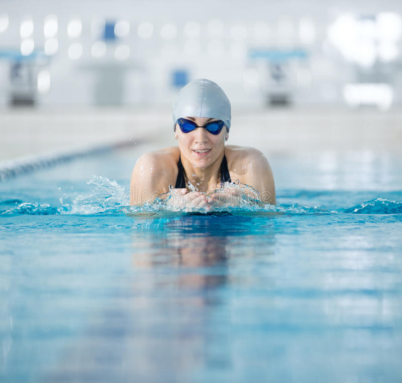 Young girl in goggles swimming breaststroke stroke style. Young woman in goggles and cap swimming breaststroke stroke style in the blue water indoor race pool royalty free stock photography