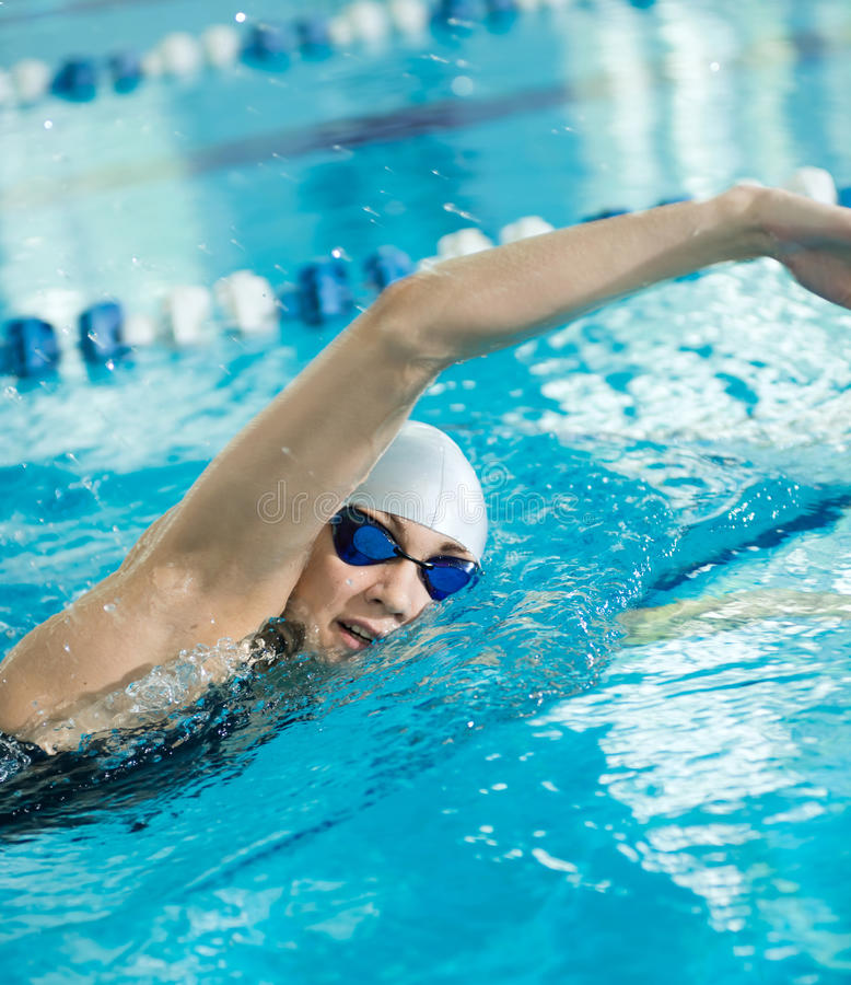 Young girl in goggles swimming front crawl stroke style. Young woman in goggles and cap swimming front crawl stroke style in the blue water indoor race pool royalty free stock photo