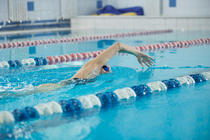 Young girl in goggles swimming front crawl stroke style. Young woman in goggles and cap swimming front crawl stroke style in the blue water indoor race pool stock photo