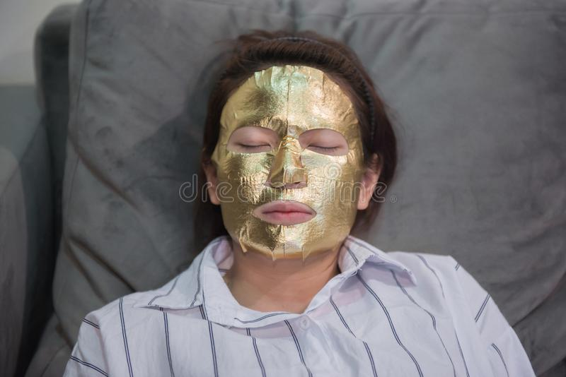 Young girl with gold facial mask stock photography